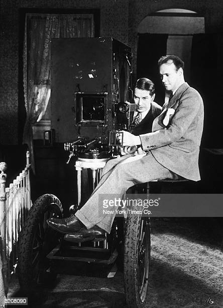 Paramount Studios cinematographer at George Folsey sits on the truck of a soundproof 'suitcase' camera for talking pictures while French actor...