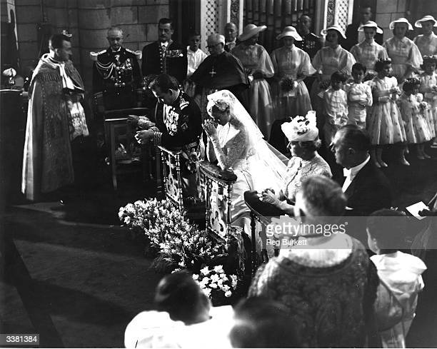 American actress Grace Kelly and Prince Rainier III of Monaco praying during their wedding ceremony at Monaco Cathedral