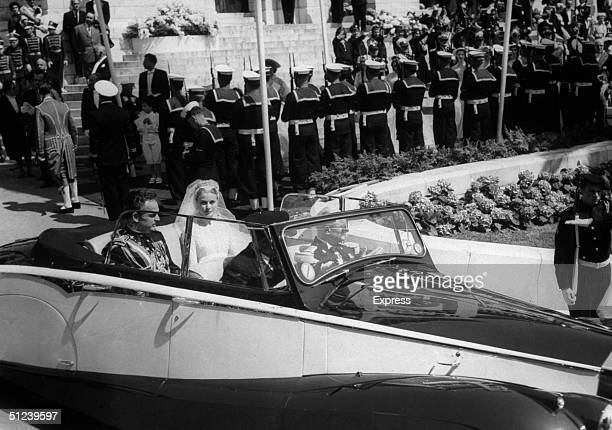 American actress Princess Grace and her husband Prince Rainier III are driven through the streets of Monte Carlo in a convertible car following their...
