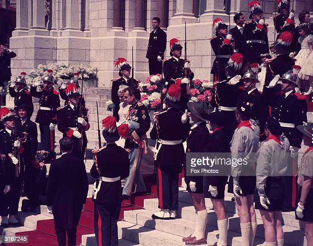 Prince Rainier of Monaco and Princess Grace walk down the steps of the cathedral after their wedding flanked by a military guard and members of a...