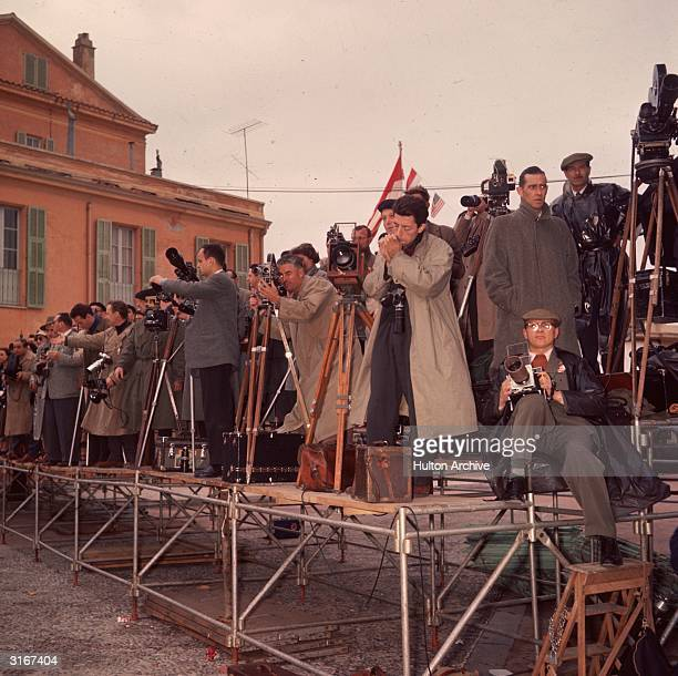 Standing on a temporary platform photographers at the wedding of Prince Rainier of Monaco and Grace Kelly check their equipment before the...