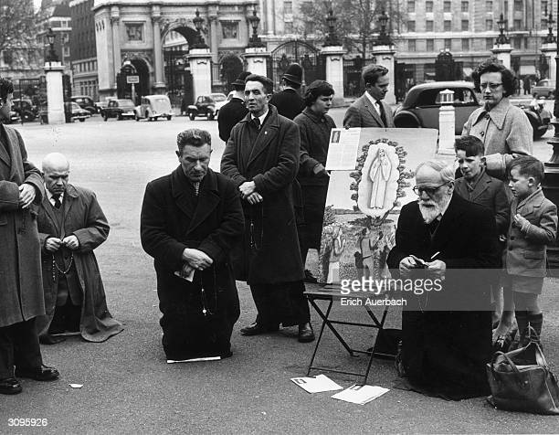 A group of Catholics with rosaries kneeling around a painting of the 'miracle at Fatima' in London's Hyde Park On May 13th 1917 and on several...