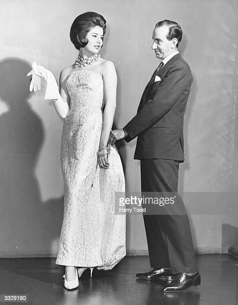 Italian designer Emilio Pucci, Marchese di Barsento, adjusts a white and gold strapless evening dress in 'Emilioform' silk elastic fabric, worn by...