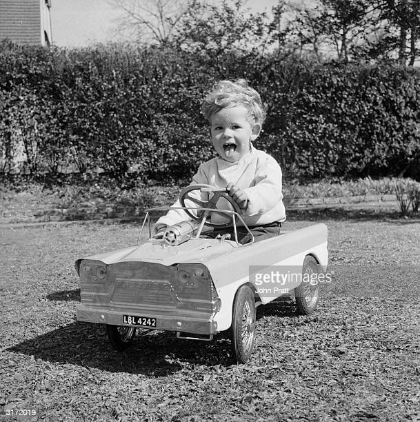 Two year old Timothy Pratt is more than a road hazard in his new 1961 de luxe model car and can often be seen terrorising the local gardens and parks