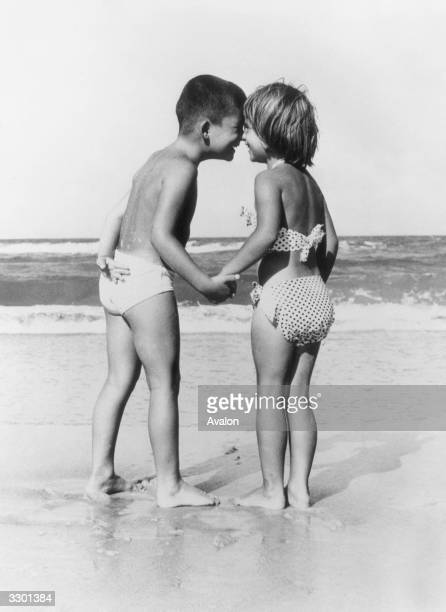 A little boy and girl in swimwear holding hands on the beach