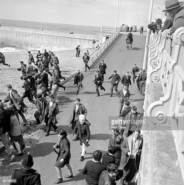 A mounted policeman chasing a group of teenagers on to the beach at Brighton during skirmishes between mods and rockers
