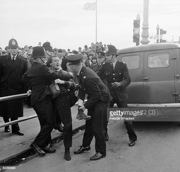 Police arresting people during clashes between mods and rockers at Brighton