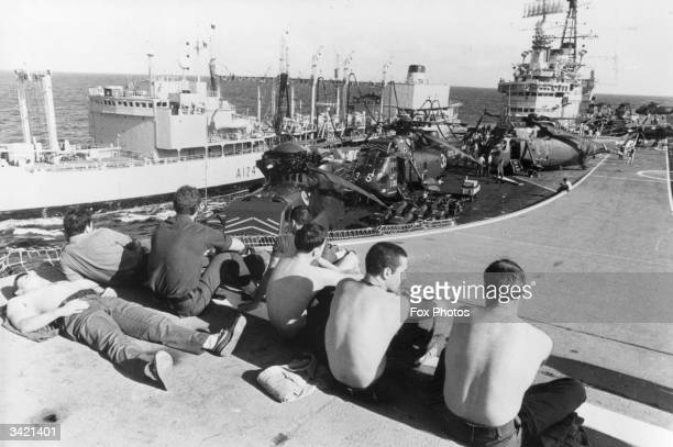 Marines relaxing on the 'ski jump' ramp of HMS Hermes as she is replenished at sea by a Royal Fleet auxiliary vessel on the way to the Falkland...