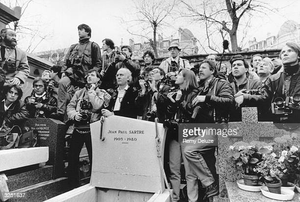 Photographers and journalists cluster round the grave of French philosopher and writer JeanPaul Sartre on the day of the funeral of his longtime...