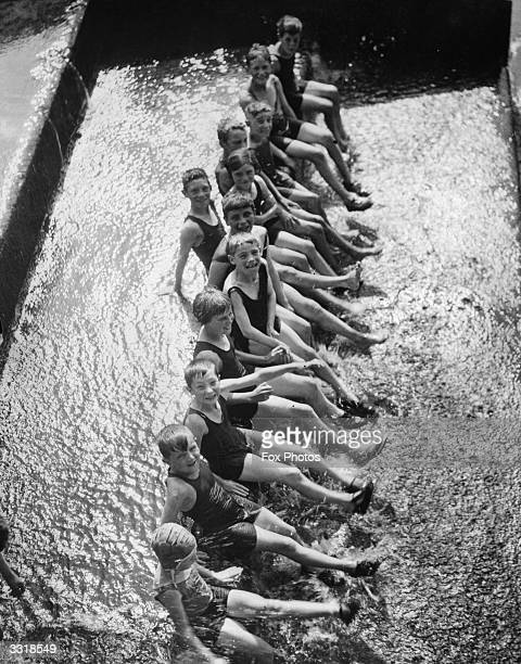 A group of children sitting on the steps of Teddington Weir Middlesex to keep cool in the summer heat