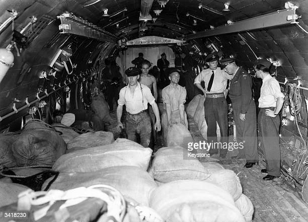 American airforce personnel unloading sacks of flour from a C74 Globemaster cargo plane at Gatow Berlin as part of the Berlin Airlift