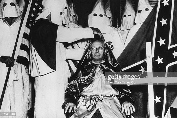 Hooded Klansmen holding American and Confederate flags surround Lycurgus Spinks as he is crowned imperial emperor of the Ku Klux Klan during a...