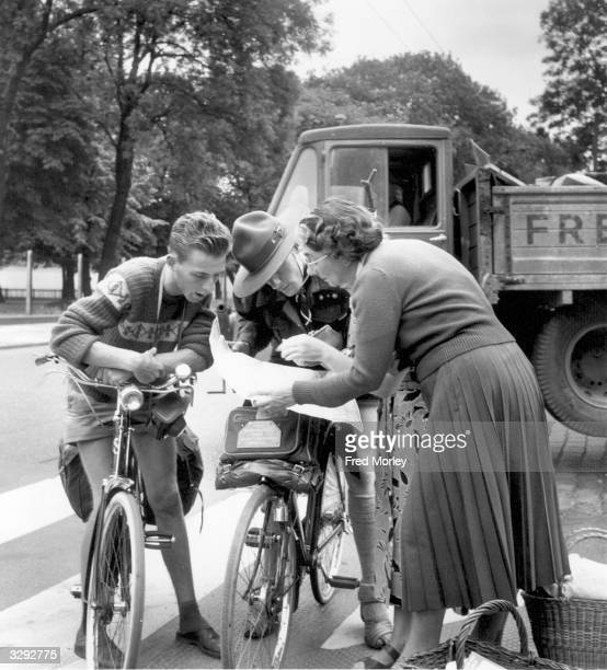A London housewife gives directions to two visiting overseas scouts sightseeing on their bicycles