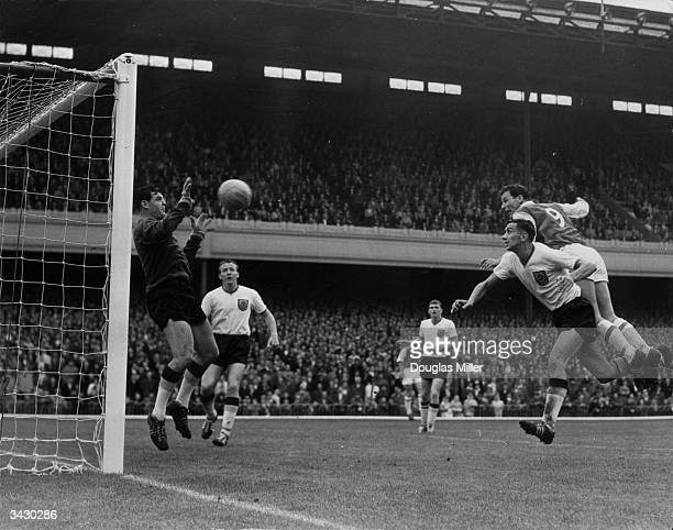 Arsenal forward Mel Childs heading the ball past the Burnley goalkeeper Adam Blacklaw during a game at Highbury London
