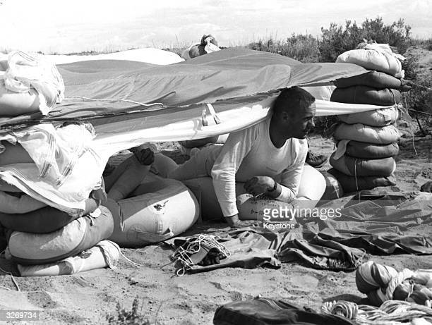American astronaut Neil Armstrong peers from a makeshift tent in Nevada during an intensive three day desert training course for future space...