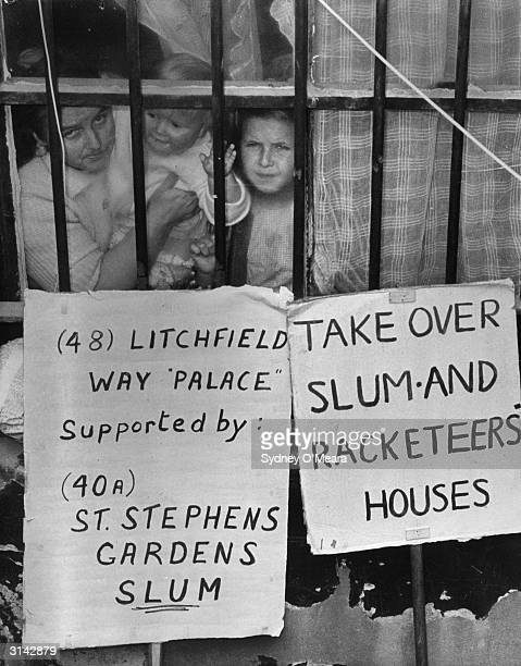 Mrs Cobb and her children peer through a window of the house where they are squatting in St Stephen's Gardens Paddington London Outside are placards...
