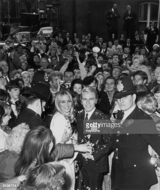 Pop singer and actor Adam Faith with his wife Jackie Irving surrounded by fans and police after their wedding at Caxton Hall registry office in London