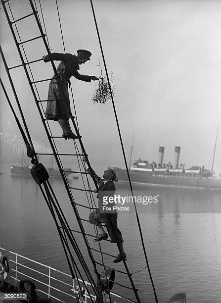 A passenger on the LNER steamer Vienna climbs up the rigging to accept a tempting invitation from a young lady with a bunch of mistletoe The fact...