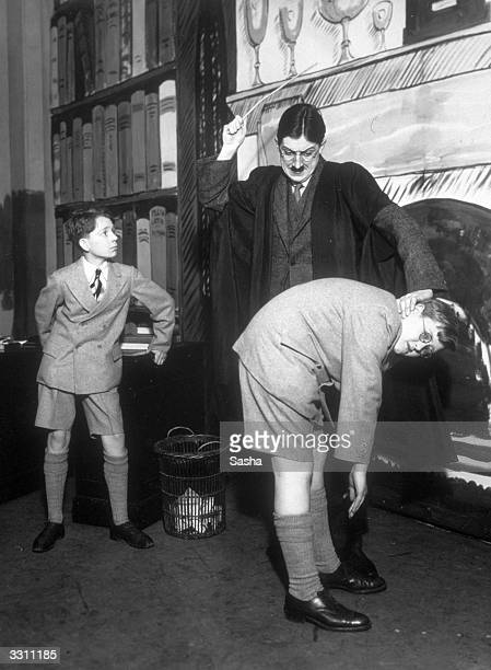 A teacher canes a pupil in a scene from the play 'What Happened to George' at Wyndham's Theatre London