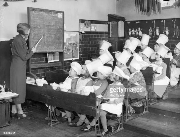 Infants at Torringdon Road School in Catford London learn how to make Christmas puddings for the poor children of other schools
