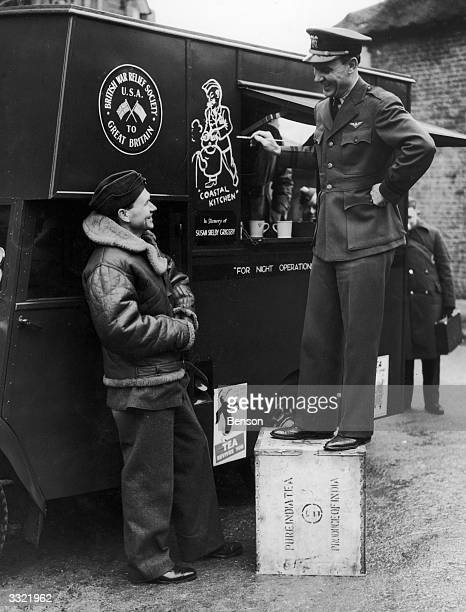 A Lieutenant of the US Naval Air Force paints a 'coastal kitchen' design on a tea car presented to the RAF Coastal Command by the British War Relief...