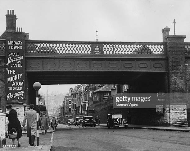 Cars drive away from the centre of Chatham, passing under a road bridge.