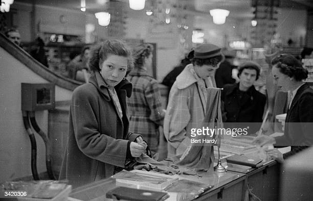 A shoplifter looking around a department store to check if anyone is watching her Original Publication Picture Post 6835 What Makes A Shoplifter pub...