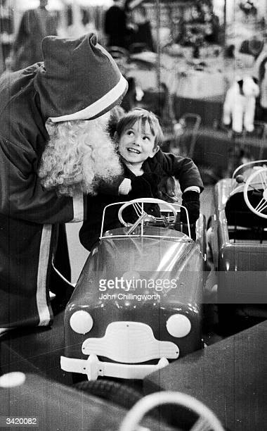 Picture Post reporter Denzil Batchelor in costume as Father Christmas at Harrods department store in London asks a little boy what he wants for...