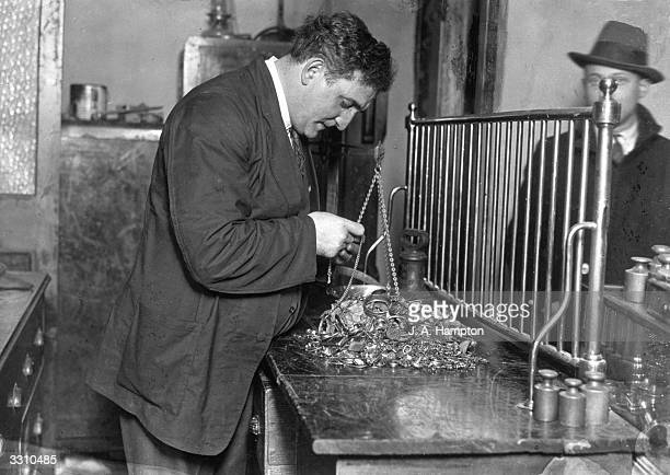 Mr Abelson examining some of the gold articles he purchased from the public after the lifting of the Gold Standard in Britain led to hundreds of...