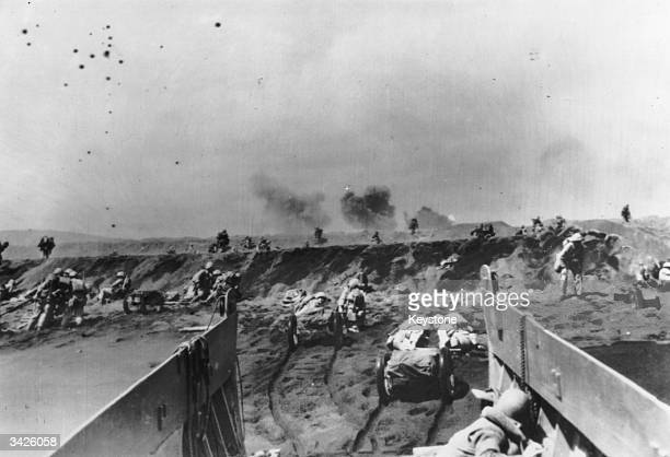 American marines storming the beaches of Iwo Jima dragging mobile artillery with them