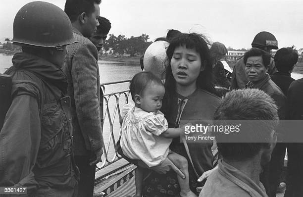 A Vietnamese refugee crossing the 'Perfume River' with her baby with other refugees during the Vietnamese War