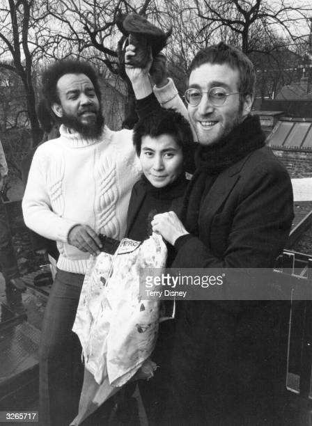 John Lennon and Yoko Ono give their newly cut hair to black power leader Michael X in return for a pair of Muhammad Ali's bloodied boxing shorts