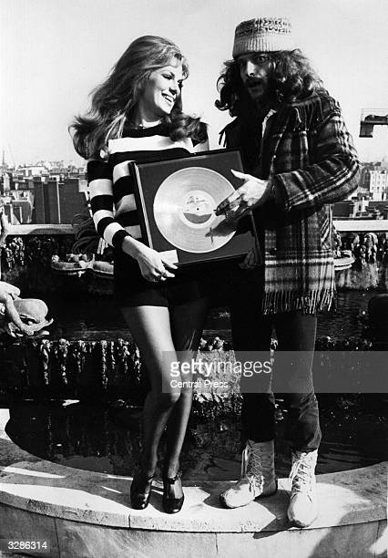 Ian Anderson singer and flautist in folkrock group Jethro Tull is awarded a gold disc by actress Julie Ege on the roof of the Dorchester Hotel in...