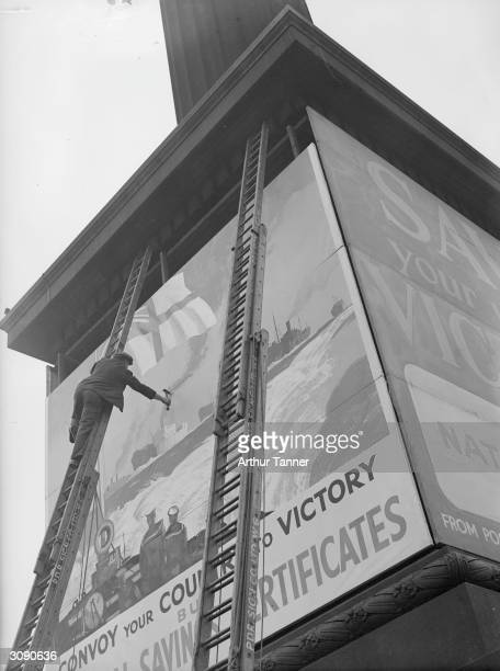 Men at work erecting a giant poster on Nelson's Column in London advertising the National Savings Campaign