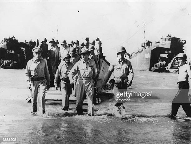General Douglas MacArthur , goes ashore from a landing craft with a party of the invading force at Luzon.