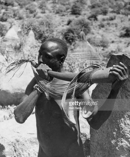 A man of the Latuko tribe from the village of Ilyeu high in the Lafit mountains above the Bongoi River blows on a rudimentary trumpet one of the...