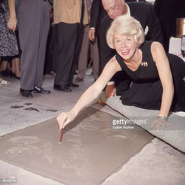 American singer and actress Doris Day smiling as she signs her name in cement by her handprints in front of Mann's Chinese Theater on Hollywood...