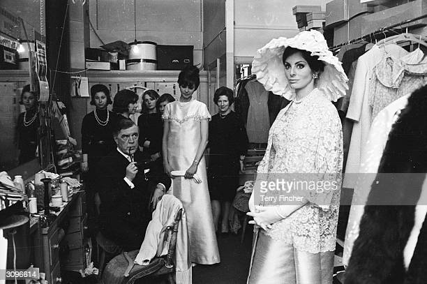 Backstage at a fashion show, Nola models a Norman Hartnell evening dress with a lace bodice and frilly hat. Hartnell himself keeps an eye on...