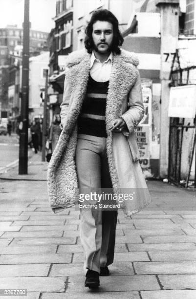 Michael Cooper in his sheepskin coat walks along a London street