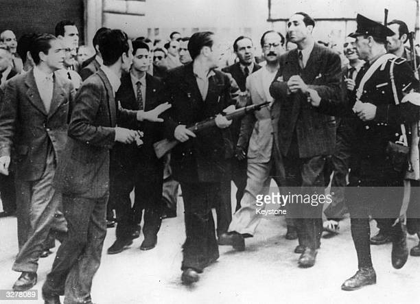 In Rome an angry crowd of armed antiFascist civilians helps a policeman escort an ex'Big Shot' of the Fascists to the jail where he will be held...