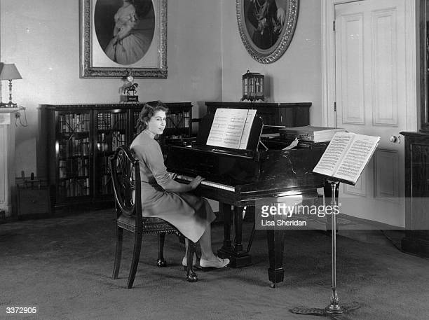 Princess Elizabeth playing a piano in the State Apartments at Buckingham Palace