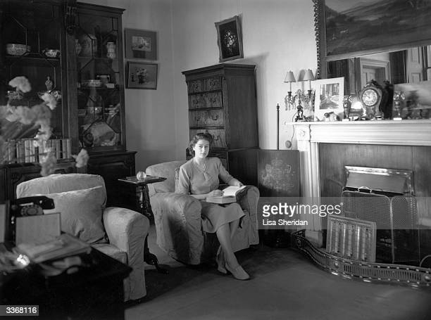Princess Elizabeth reading in her apartment at Buckingham Palace.