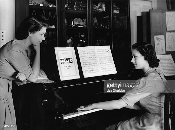 Princess Elizabeth watches her sister, Princess Margaret Countess of Snowdon play a Brahms Waltz on the piano in the school room at Buckingham Palace.