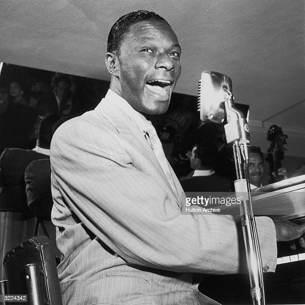 American pop singer and pianist Nat 'King' Cole plays piano and sings into a microphone An unidentified bassist plays behind him