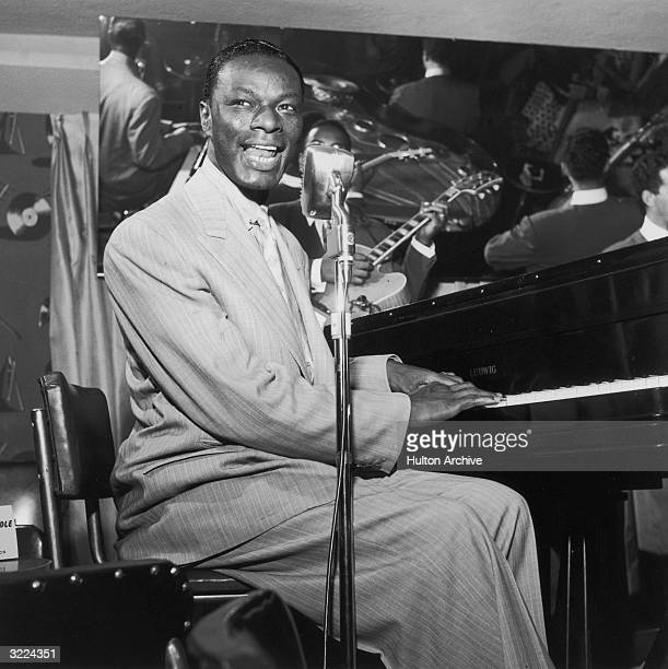 American pop singer and pianist Nat King Cole plays the piano and sings into a microphone during a concert performance Several musicians are...