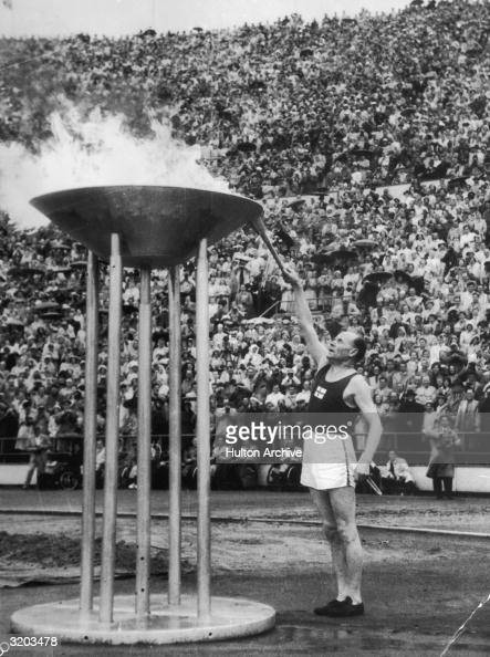 Finnish runner Paavo Nurmi a former gold medalist lighting the Olympic flame at the opening ceremonies for the Summer Olympic Games Helsinki Finland