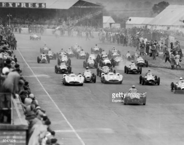 Driver Frolian Gonzalez leading the pack at the Silverstone Grand Prix. Close behind are Stirling Moss and Mike Hawthorn while Juan Manuel Fangio and...