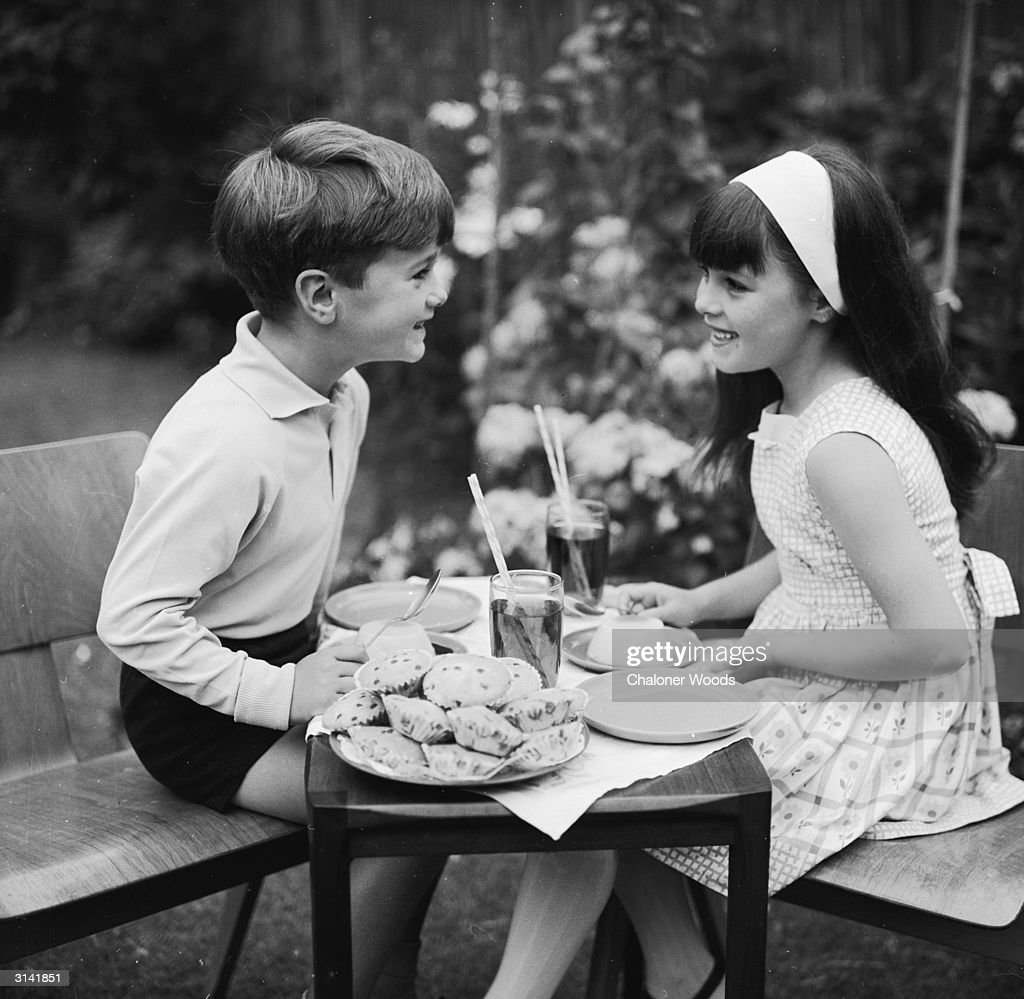 A boy and a girl share a teatime snack of cakes and soft drinks.