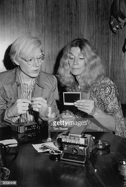 American pop artist Andy Warhol and American actor Sylvia Miles sit at a table looking at a Polaroid photograph he took during a Mother's Day party...
