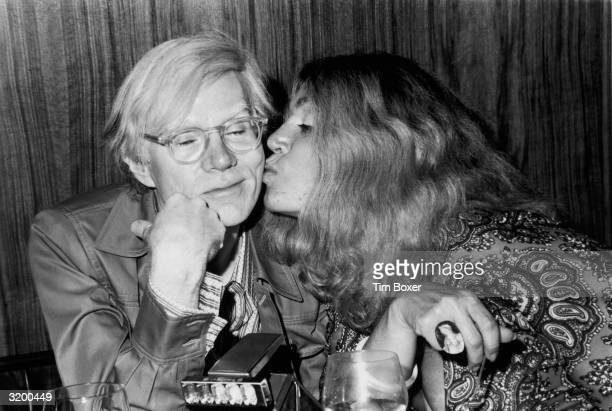 American Pop artist Andy Warhol receives a kiss on the cheek from American actor Sylvia Miles during a Mother's Day party at the Four Seasons Hotel,...
